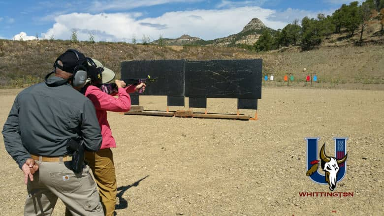 NRA Instructor closely watches a woman safely shooting a defensive shotgun at the Whittington University Range