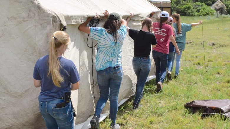 A group of young people working together to setup a tent.