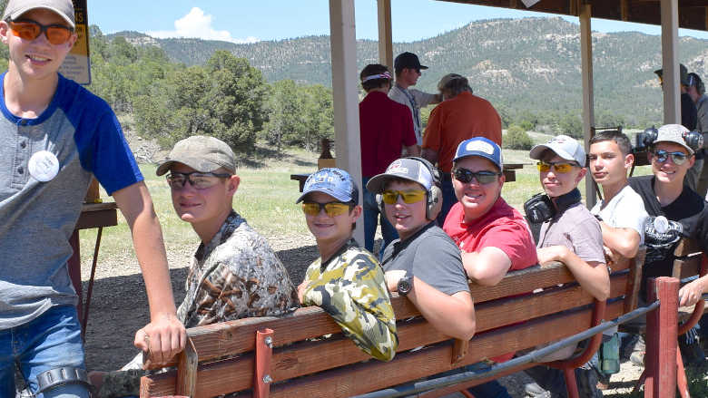 Group of young people sitting on a bench at a gun range in the mountains.