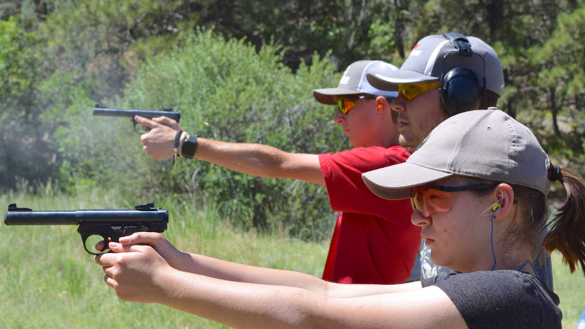 Youths shooting pistols at an outdoor range with ear and eye protection
