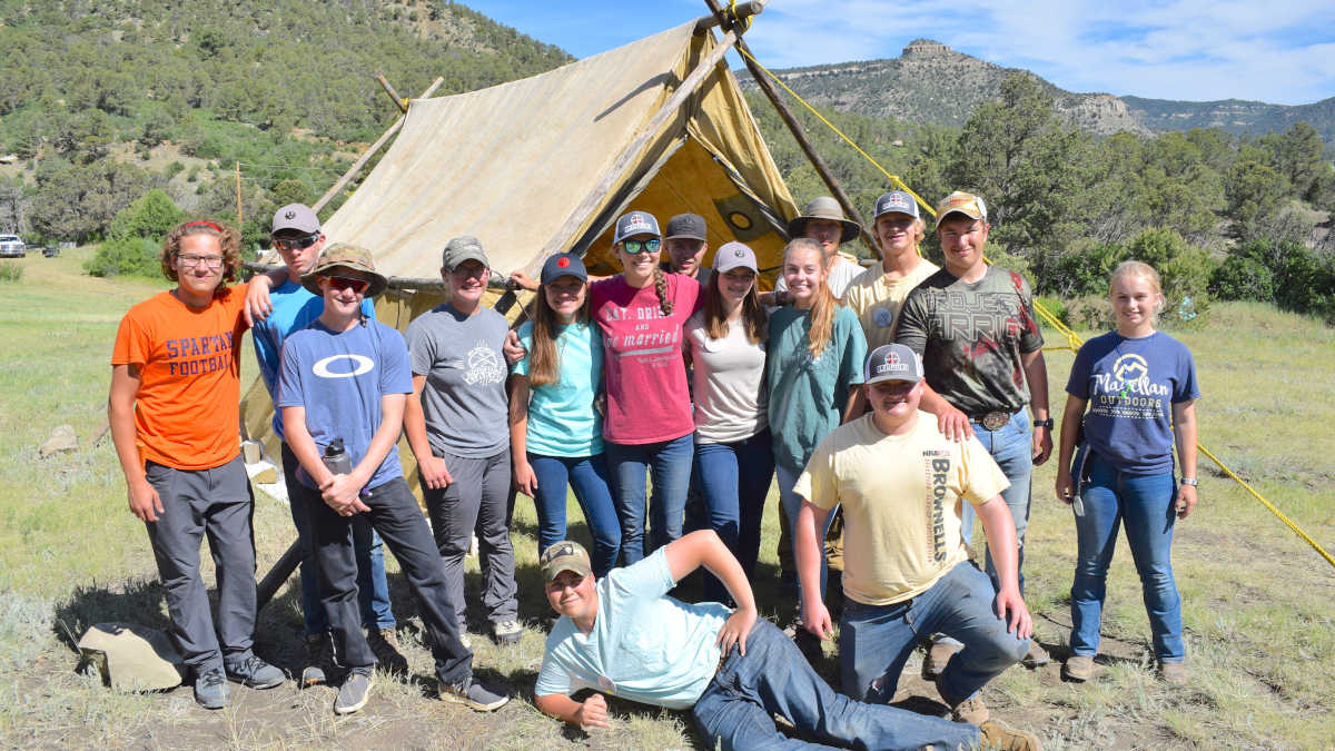 Adventure Camp attendees celebrating their building of a tent in the mountains at the NRA Whittington Center