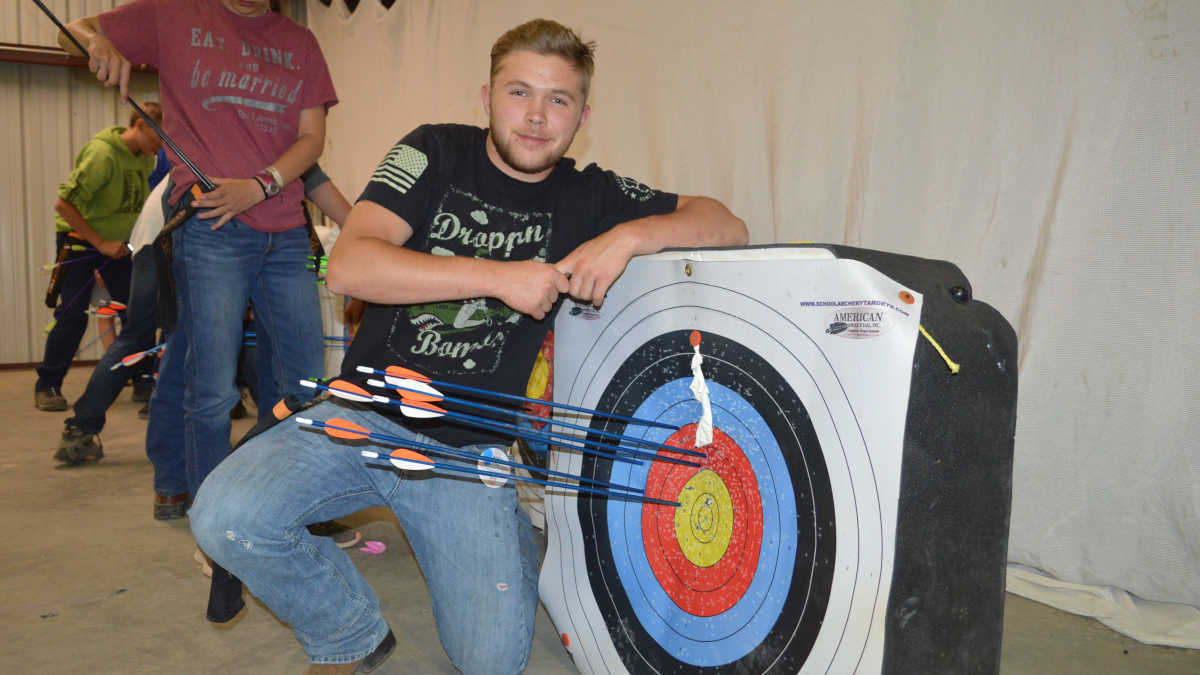 Adventure Camp attendee proudly displaying is archery skills at the NRA Whittington Center