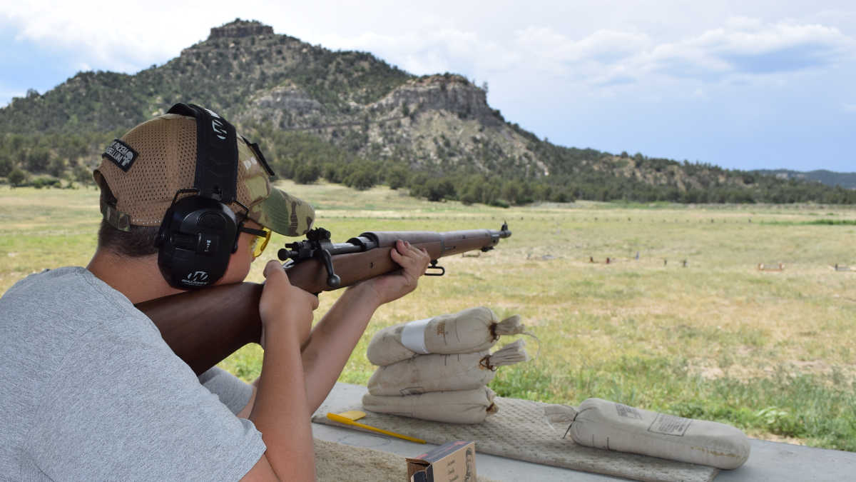 Young man shooting a rifle at an outdoor range at the NRA Whittington Center Adventure Camp in New Mexico
