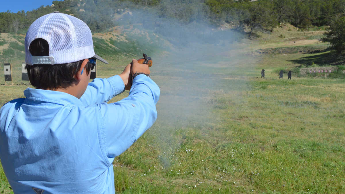 Young man shoots a musket pistol at the NRA Whittington Center Adventure Camp in the mountains of New Mexico