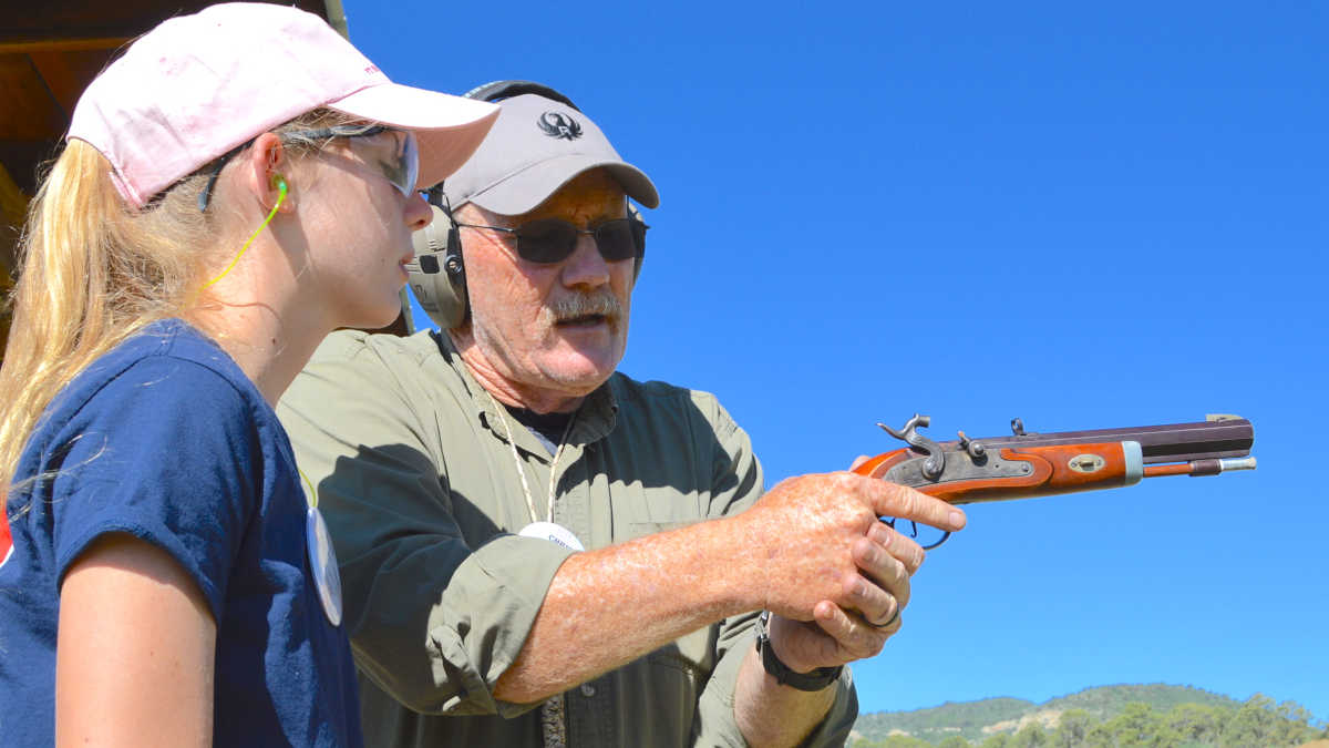 Expert instructor shows a girl in a pink hat how to properly handle a musket pistol at the NRA Whittington Center