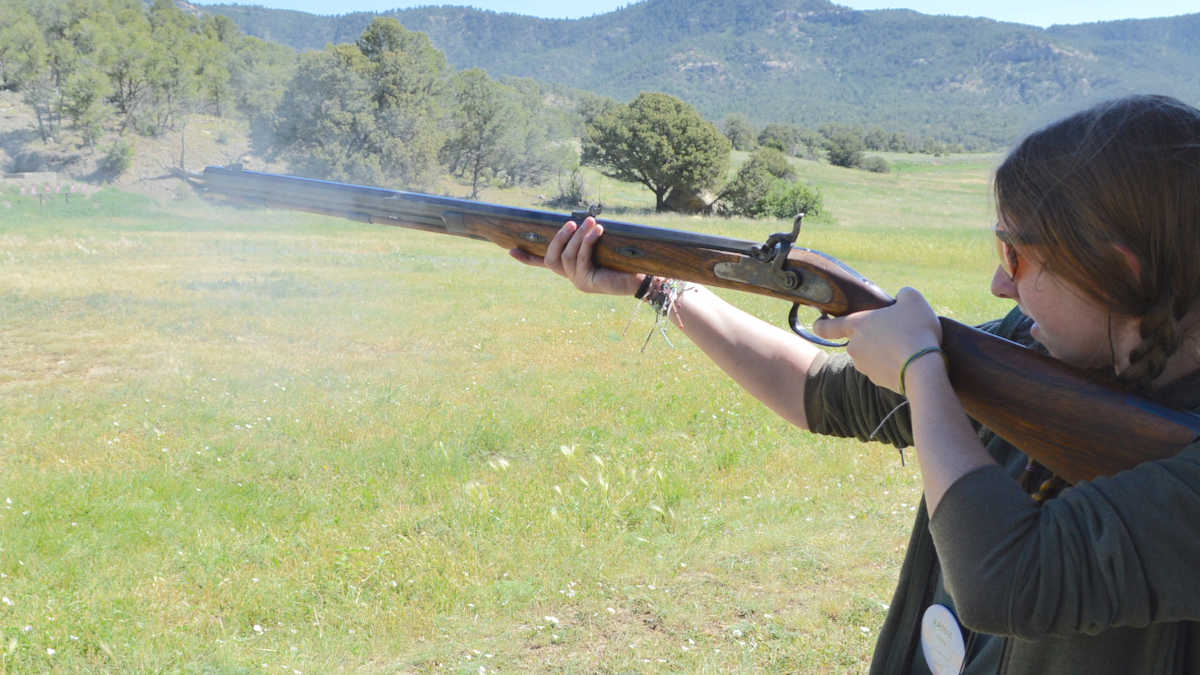 Young girl shoots a musket rifle in the mountains of New Mexico while attending the NRA Whittington Center Adventure Camp
