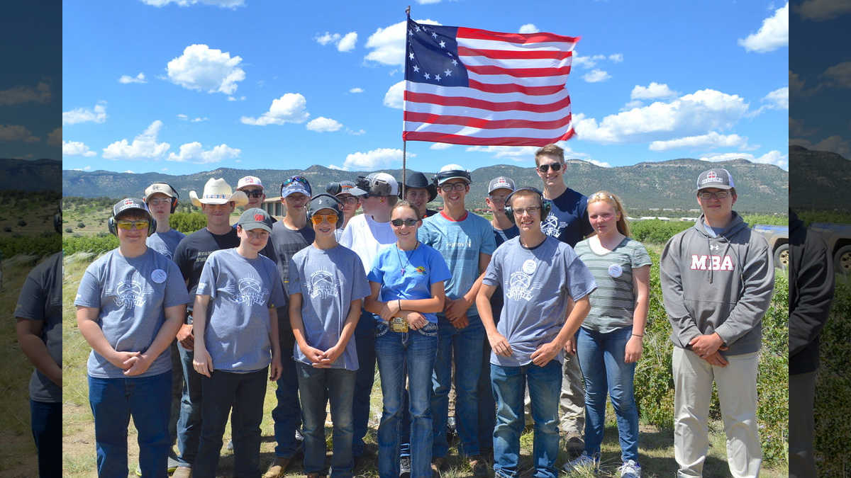 Adventure Camp attendees proudly standing with the United States Flag in the mountains of New Mexico