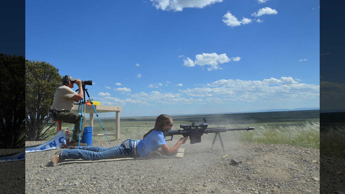 Under the watchful eye of NRA instructors, a young girl fires a sporting rifle at a long range target