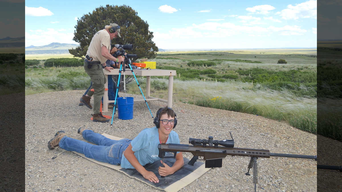 Excited youth reacts to shooting a sporting rifle at long range under the watchful eye of an NRA Instructor