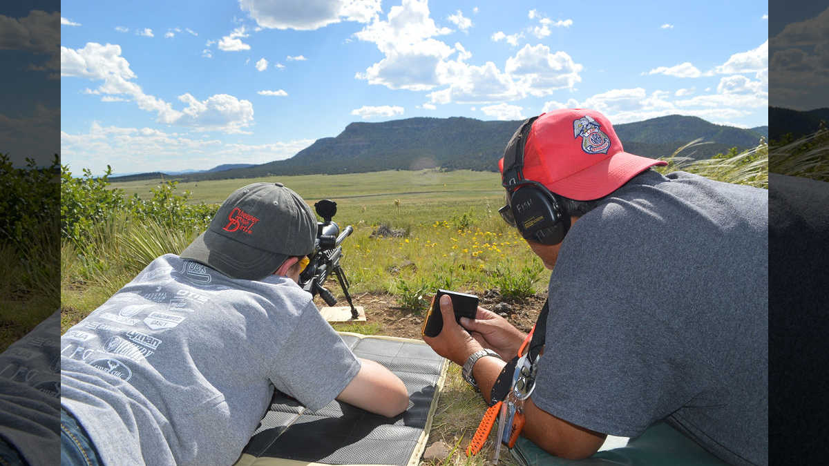 Two youths work together to sight in a rifle in the mountains of New Mexico at the NRA Whittington Center Adventure Camp