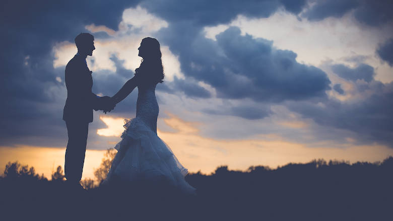 Bride and Groom holding hands at sunset in the mountains